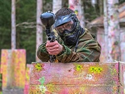 Image of a man standing behind a wooden fence in camouflague clothing and holding a paintball gun wearing mask