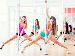 Image of a group of women dancing on poles in a studio wearing heels
