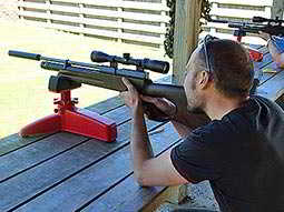 Close up of a man aiming with an air rifle on a red stand, set on a wooden table