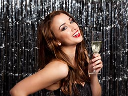 A woman in front of a glittery background, smiling and holding a drink