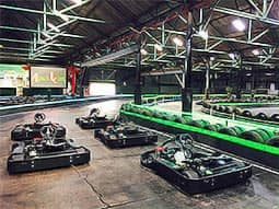 Three people in go karts on an indoor track