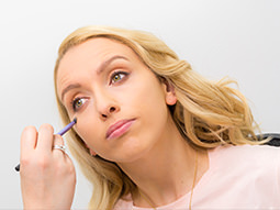 A girl receiving a make over from a professional make up artist