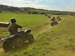 A group of people driving quad bikes through a field