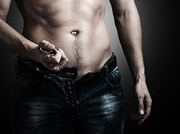 Image of a man with no top on puling the belt off his jeans