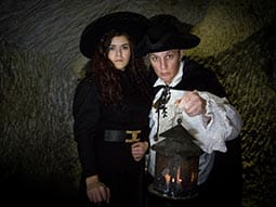 Image of a man and woman in a cave holding a lantern wearing hats