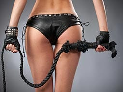 Image of a womans backside in a leather pair knickers with leather gloves on holding a big leather wip