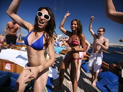Image of a group of people dancing and drinking on a boat