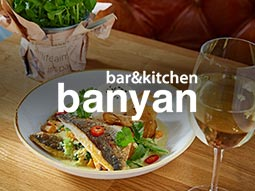 A plate of food with a glass of wine next to it and the Banyan logo over