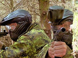Two people aiming with paintball guns
