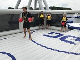 Some people wearing wetsuits and holding balls on inflatables