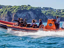 A group of people on a power boat, with cliffs in the background