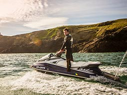 A man on a jet ski with land in the background