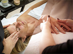 A split image of a woman receiving a head massage and a woman receiving a hand massage
