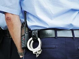 A close up of the back of a policeman, with handcuffs on his belt