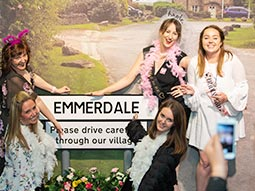 A group of women standing next to an Emmerdale sign with an image of the set in the background