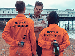 A man dressed in an orange boilersuit carrying a tray of drinks, with people in jail cells in the background