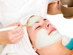 Image of a woman lying down getting a face mask applied