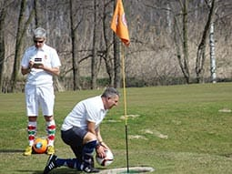 Imaages of two men playing footgolf