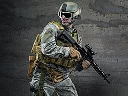 Image of a guy weating camoflague clothing with a helmet and goggles holding a gun