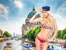Image of a woman in a bikini wearing a sailor hat and berlin as her backdrop