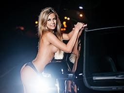 Image of a woman in her thong standing leaning onto a black limo