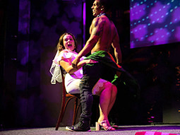 A stripper giving a bride to be a lap dance on stage
