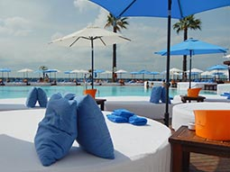 A beach club with seating around a pool
