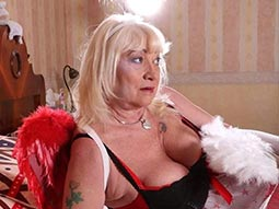 An old woman in sexy lingerie on a bed