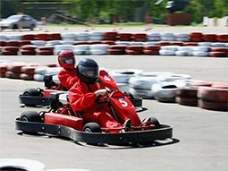 Two people racing in red go karts