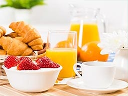 A bowl of pastries and strawberry's alongside a glass of orange juice on a table