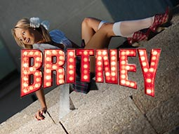 A girl lying on a pavement dressed in a school uniform and a Britney sign over