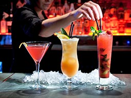 Three cocktails on a bar, with a bartender putting straws into one of them