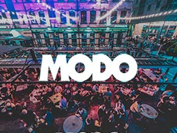 A birds eye view of a nightclub with green and purple lighting and the Modo logo over