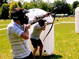 Two people hiding behind an inflatable obstacle, holding bows with rubber tipped arrows
