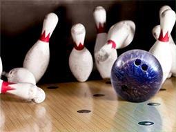 Image of a bowling bowl knocking down pins