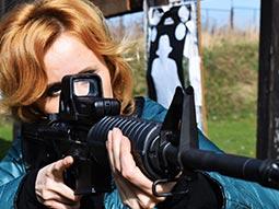 A woman aiming a gun