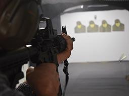 A close up of a man aiming a gun at targets