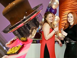 A split image of a chocolate fountain and two women holding glasses with prosecco and balloons in the background