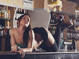 A woman in black pants, knee high socks and heels, lying on a bar