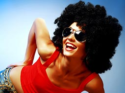 Woman bending forwards in a red vest, afro wig and sunglasses