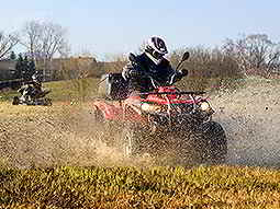 A quad bike being driven through a wet field, with another quad bike in the background