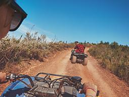 Image of two people on a track driving quad bikes in the warm sunshine