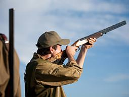 Image of a man aiming a gun into the air wearing a baseball cap