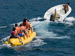 Image of a group of people being pulled on a banana inflatable by a speedboat