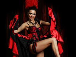 Image of a woman dressed in a burlesque outfit dancing holding her dress