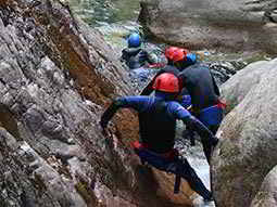 A group of people walking through a small crevasse and wading into a shallow river
