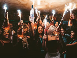 A group of people in a nightclub holding up bottles of vodka and sparklers