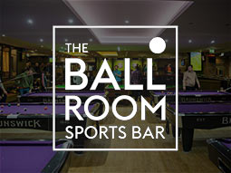 A room with various pool tables, lit up with spotlights from the ceiling and The Ball Room Sports Bar logo over