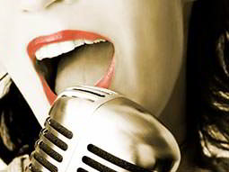 A close up of a womans mouth singing into a microphone