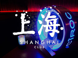 A bottle of Ciroc vodka on a table, in low lighting with the Shanghai logo over
